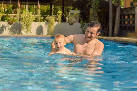 bather: Happy family father and son. Dad teaches his son to swim