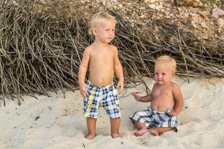 Toddler Boys Sitting on the beach in the tropics