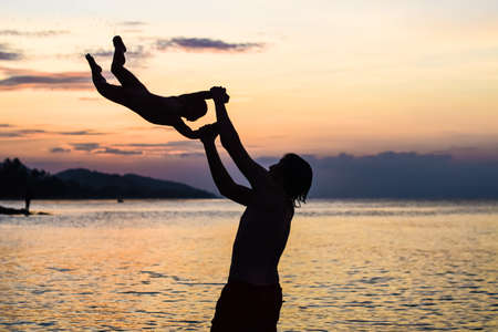 throw up: young happy father holding up in his arms little son putting him up at the beach in barefoot standing in front of sea waves wet sand having fun with the kid in Summer sunset coast.