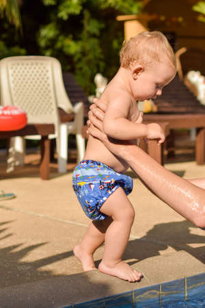 Toddler child goes to the hands of his father to swim in the pool
