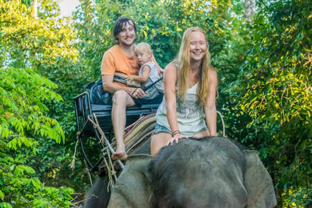 Happy family riding on an elephant, a young woman sitting on the elephants neck