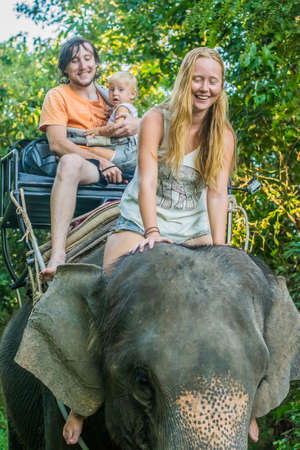 ajutthaya: Happy family riding on an elephant, a young woman sitting on the elephants neck