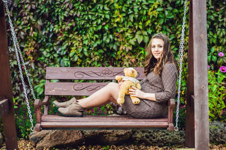 natural childbirth: A pregnant young woman sitting on a swing, with a teddy bear. pregnant woman relaxing in the park. Lovely prospective mother