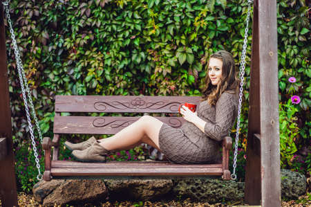 lovely pregnant woman: A pregnant young woman sitting on a swing, with a cup of tea. pregnant woman relaxing in the park. Lovely prospective mother Stock Photo