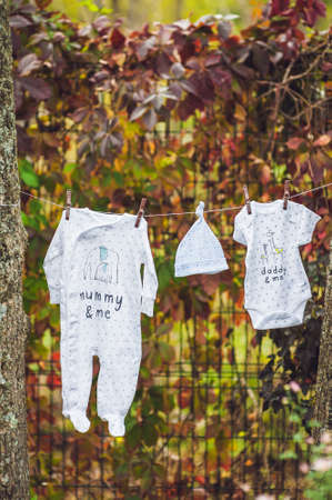 summer wear: Newborn baby on a pile of clean dry towels. New born child after bath in a towel. Family washing clothes. Kids wear hanging on a line outdoors in summer garden. Infant apparel, textile for children. Vertical frame