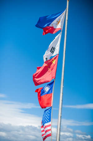 Flags of different countries flagstaff against the blue sky