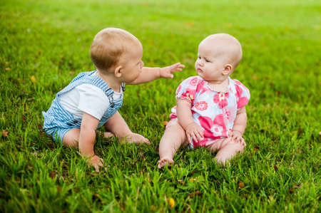 9 months old: Two happy baby boy and a girl age 9 months old, sitting on the grass and interact, talk, look at each other. Kids are resting on a hot summer day on the grass. Stock Photo