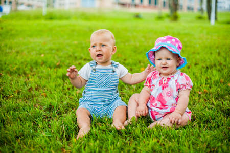 Two happy baby boy and a girl age 9 months old, sitting on the grass and interact, talk, look at each other. Kids are resting on a hot summer day on the grass. Stock Photo