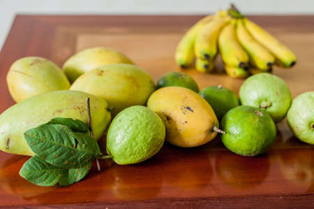 guayaba: Fruits on the wooden table. Mangoes, bananas, tangerines, guava Useful food concept