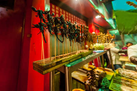 exotic food: The Chinese market, fried scorpions on stick, exotic food concept Stock Photo
