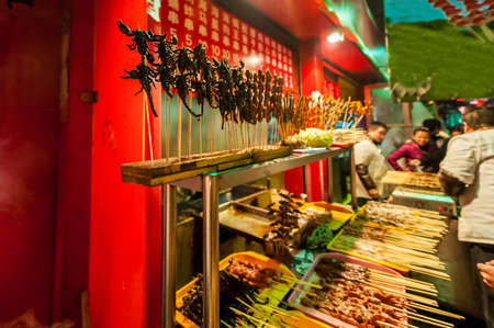 BEIJING, CHINA - DEC 06, 2011: Chinese market in winter, fried scorpions on stick, exotic food concept