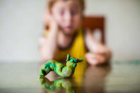 nurser: childrens creativity. child sculpts from clay.Cute little boy moulds from plasticine on table. Childrens creativity concept