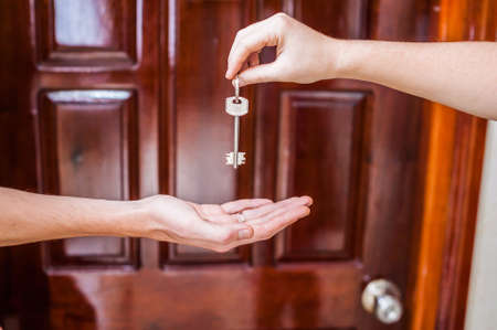owning: Female hand giving a key to the house a mans hand on a background of a wooden door. Owning real estate concept.