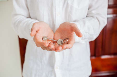 owning: Mens hands hold house key on a background of a wooden door. Owning real estate concept. Stock Photo