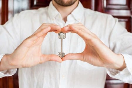 owning: Mens hands hold house key in the form of heart on the background of a wooden door. Owning real estate concept.