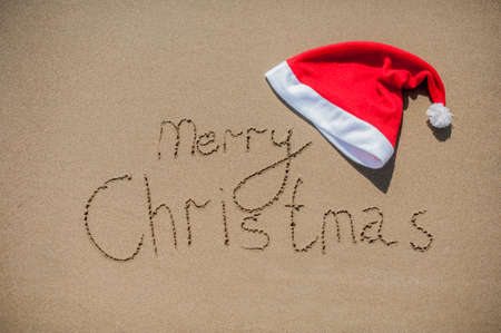 clima tropical: inscription on the wet sand and cap of Santa Claus Christmas in tropical climate concept