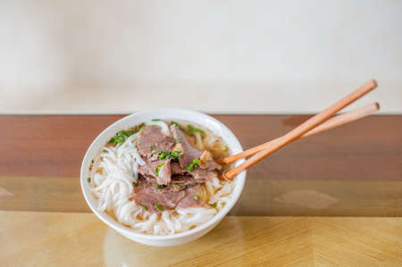Traditional Vietnamese beef soup pho on a wooden background. Vietnamese food concept