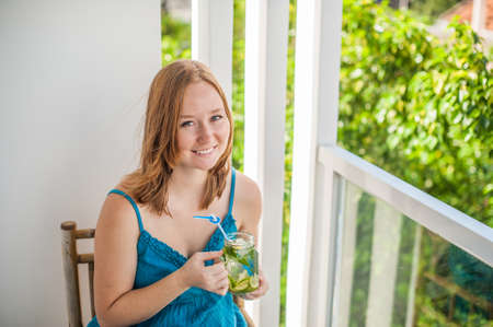 shrubbery: Red-haired woman drinking a mojito on the terrace. Vacation concept