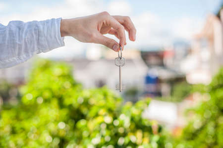 A man holding a key to the house on a background of houses in the city. Deal with the real estate concept.