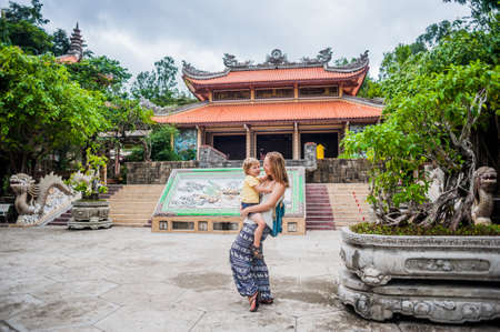 Happy tourists mom and son in Long Pagoda. Travel to Asia concept. Traveling with a baby concept. Stock Photo