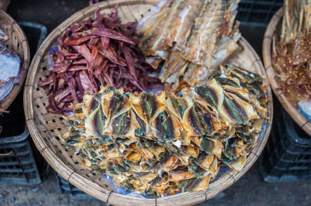 phen: Dried fish on a wicker basket in a market in the Vietnam. Asian food concept.