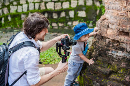 stabilizer: Man videographer and his son shoots video in the electronic stabilizer, steadycam To shoot at Po Nagar Cham Tovers. Digital technology concept. Devices for shooting video concept. Asia Travel concept. Stock Photo
