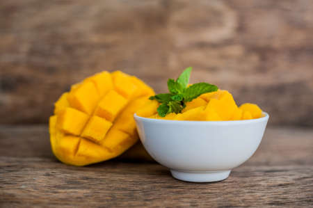 cold cut: Mango fruit and mango cubes on the wooden table. Tropical fruit concept.