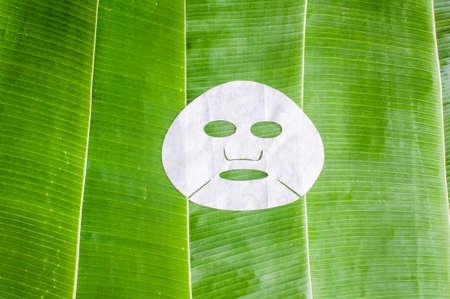 바나나 잎의 배경에 시트 얼굴 마스크입니다. 아름다움과 피부 관리 개념