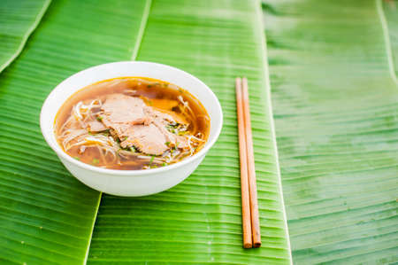 A bowl of Traditional Vietnamese beef soup Pho Bo on banana leaf background. ethnic meal. Vietnamese food concept
