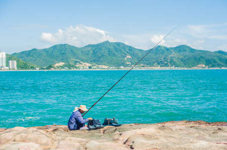 Vietnamese fishermen sitting on the edge of a cliff and fishing. Vietnam concept Stock Photo