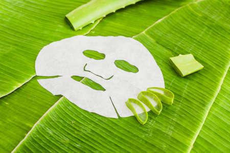시트 바나나 잎의 배경에 알로에 마스크. 유기 화장품 개념입니다. 자연 화장품 개념
