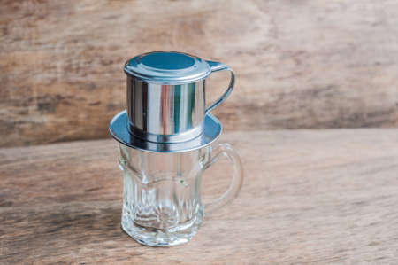 condensed: Phin traditional Vietnamese coffee maker, place on the top of glass, add ground coffee then pour hot water and wait until the coffee dripping into the glass. Stock Photo