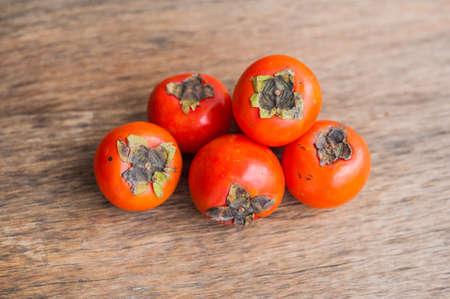 Ripe fresh persimmon on wood board. Food ingredient. Fruits