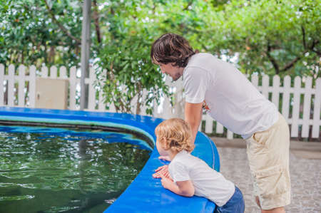 rock bottom: Father and son looks into the pool with the fishes. Rest in the aquarium concept. Ichthyology concept Stock Photo