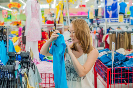 Young woman chooses shirt in shop. clothing, fashion, style and people concept Stock Photo