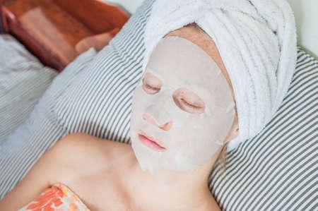 침대에 편안한 젊은 나가서는 여자. 그녀의 얼굴에 시트 마스크. 아름다움과 스킨 케어 개념