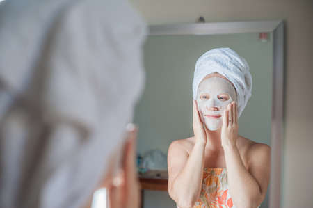 Young red-haired woman doing facial mask sheet. Beauty and Skin Care Concept