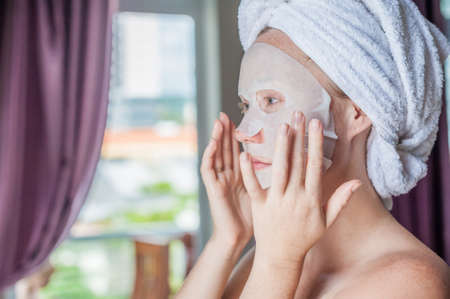 paper sheet: Young red-haired woman doing facial mask sheet. Beauty and Skin Care Concept