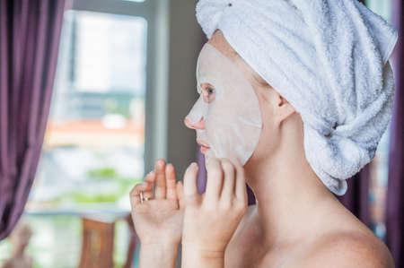 얼굴 마스크 시트를 하 고 젊은 나가서는 여자. 아름다움과 스킨 케어 개념