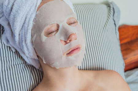 bed sheet: Young red-haired woman relaxing on a bed. Sheet mask on her face. Beauty and Skin Care Concept