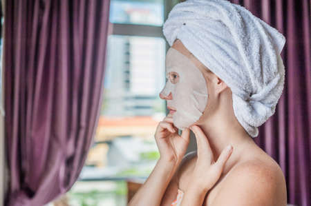 careless: Young red-haired woman doing facial mask sheet. Beauty and Skin Care Concept