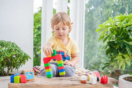 Cute little kid boy with playing with lots of colorful plastic blocks indoor. Active child having fun with building and creating of tower. Promotion of skills and creativity.
