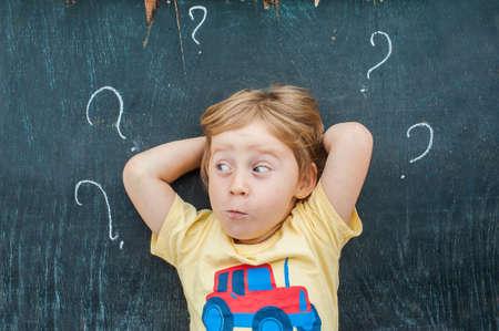 칠판에 물음표로 작은 금발 아이 소년의 상위 뷰. 혼란, 브레인 스토밍 및 선택에 대 한 개념입니다. 스톡 콘텐츠