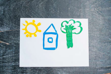 drawing paper: Childrens drawing of a house painted with colored paints. Home concept.