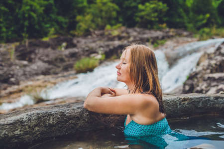 Geothermal spa. Woman relaxing in hot spring pool against the background of a waterfall. hot springs concept
