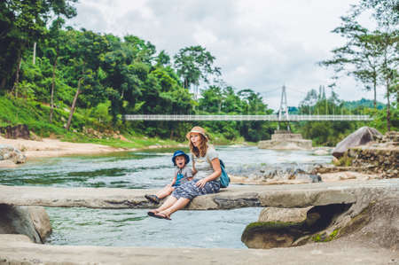 Mom and young son sitting on bridge on a background of the river. Travelling with kids concept