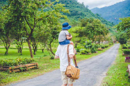rear view of father and son walking on a scenic road.
