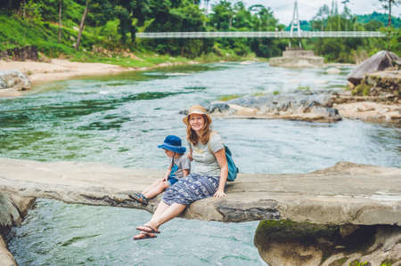 maternal: Mom and young son sitting on bridge on a background of the river. Travelling with kids concept