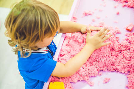 sand mold: Boy playing with kinetic sand in preschool. The development of fine motor concept. Creativity Game concept. Stock Photo