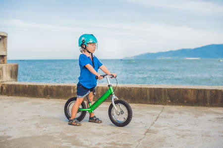 Active blond kid boy driving bicycle in the park near the sea. Toddler child dreaming and having fun on warm summer day. outdoors games for children. Balance bike concept